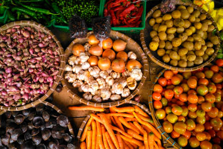 Top view pile of fresh vegetables carrots, potatoes, onion, and tomatoes on wooden table natural background. Stock Photo