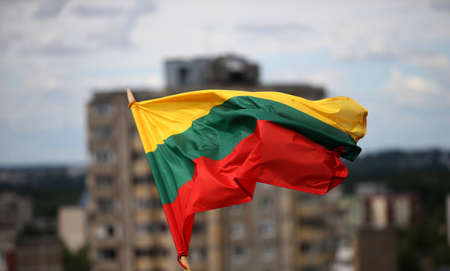 The Lithuanian flag is waving in tricolor over the city 版權商用圖片