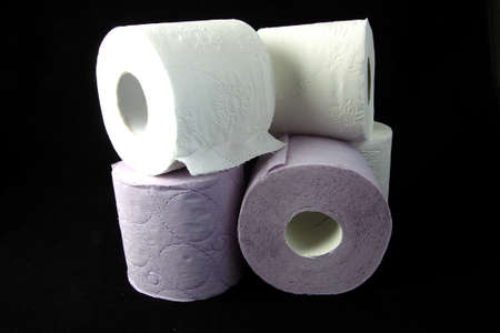 Three toilet paper rolls on a black background