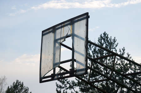 Outdoor Basketball Hoop in evening time. Outdoor basketball hoop and board damaged. Nida Lithuania