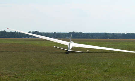 Glider plane standing on grass airport runway, at Pociunu airport, Lithuania
