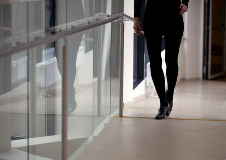 Silhouette of a beautiful woman's legs, black pants, black shoes, office