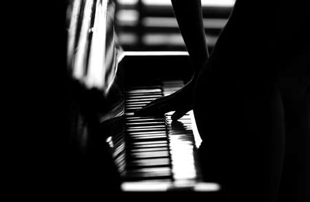 A young attractive girl plays the piano, a figure Stock fotó