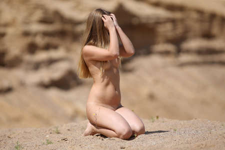 A young beautiful kneeling girl poses on the sand on a sunny day