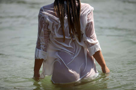 Exciting butt of a beautiful woman in a wet shirt