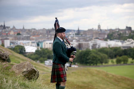 Scottish Bagpiper playing music with bagpipe at Edinburgh in Scotland 19 07 2019 Editorial