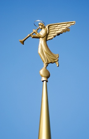 Gilded weather vane in the form of an angel blowing on the steeple at the entry of a Orthodox church. photo