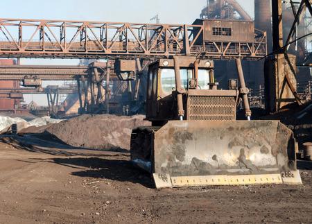 ironworks: Old bulldozer on the background grab crane ore yard ironworks