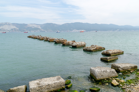 View from the embankment of the bay and a ruined pier. Novorossiysk, Krasnodar Krai, Russia - August 28, 2016.