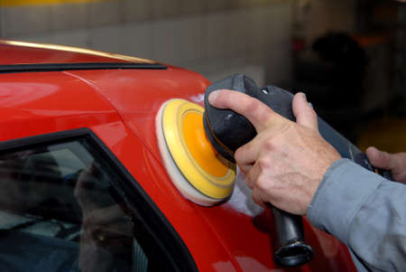 car body: Partial view of a man holding an electric machine for polishing cars Stock Photo