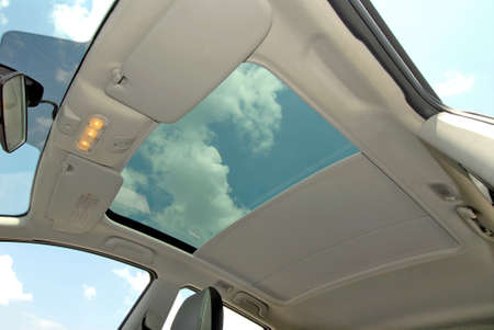 the inside of the car with a semi-open sunroof