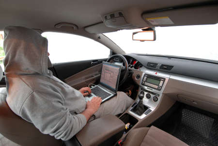 hackers: Man stealing data from a laptop sitting in a car