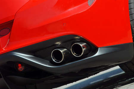 emissions: Close up of tail pipe on red sports car
