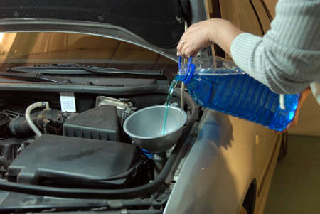 fluids: Filling the windshield washer fluid on a Car