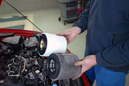 Repairman holding an old and a new air filter Stock Photo