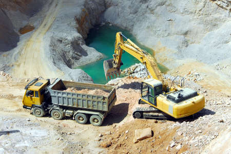 power shovel: Yellow excavator loading stones in a truck