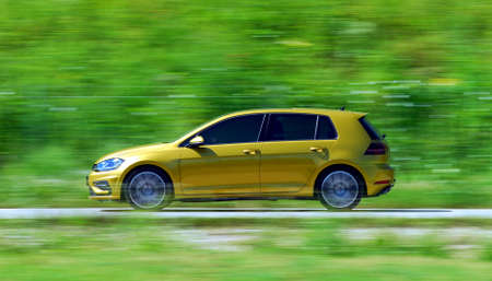 A panning shot of a speeding yelow car