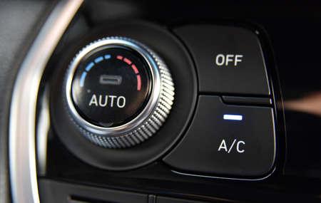 pulsante per l'attivazione dei condizionatori sul cruscotto dell'autovettura