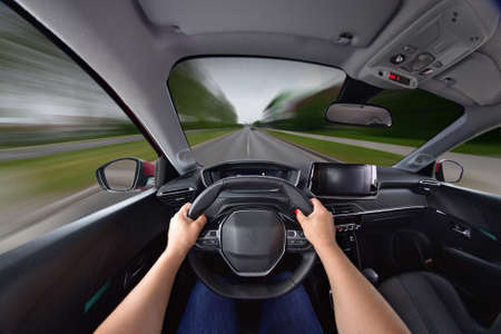 The hands of a woman holding the steering wheel while the car is moving at high speed