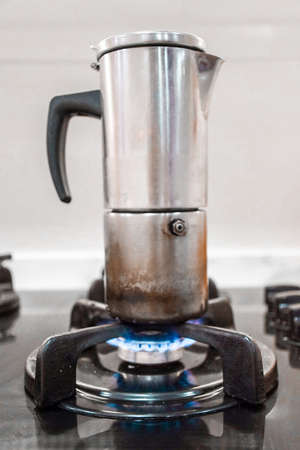 Old coffee maker on a gas stove lit with fire in a kitchen