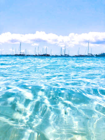 Sailing boats docked in transparent blue water