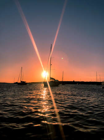 Sun rays at sunset on a sailboat at the sea