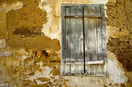 Fragment wall of old abandoned house with closed window. photo