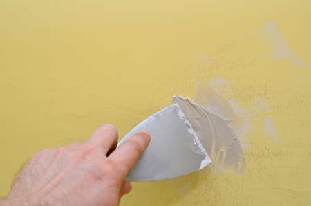 putty knives: Hand with putty knife repair damaged wall