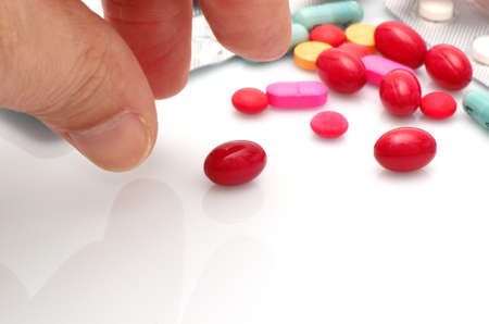 Human hand taking pill close-up.