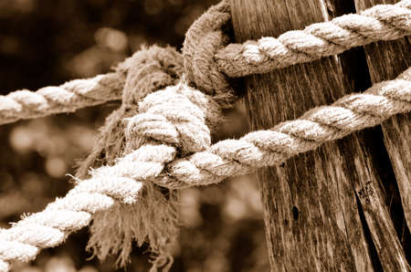 Part of old wooden fence with a rope. Sepia Stock Photo