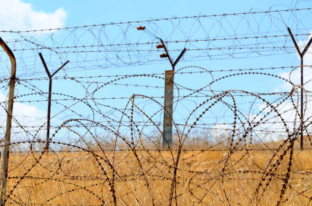 Barbed wire fence in the desert against the blue sky Stock Photo - 18511762