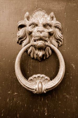 doorknocker: Old door knocker in the shape of a lions head. Sepia Stock Photo