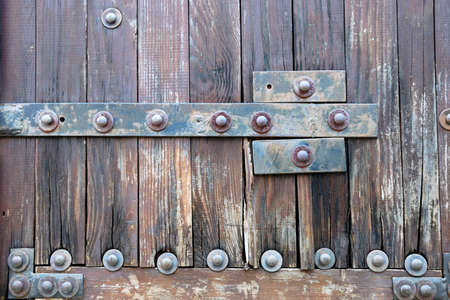 Lower part of an old heavy wooden door in ancient house  photo