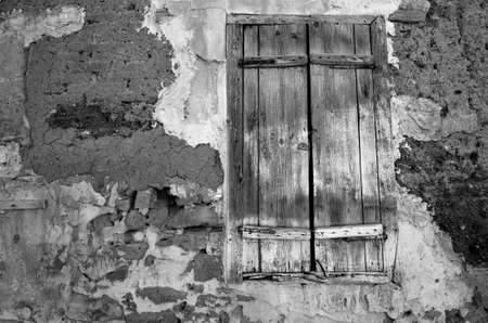Fragment wall of old abandoned house with closed window. B&W photo