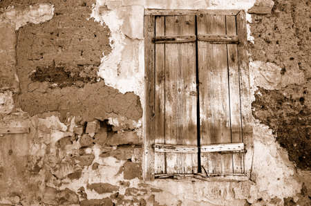 Fragment wall of old abandoned house with closed window. Sepia Stock Photo