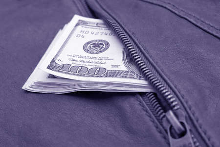 Lot of dollars in a pocket of leather jacket. Stock Photo