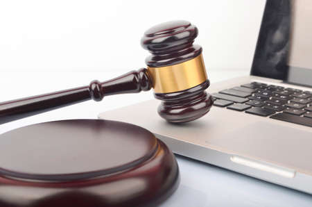 Cyber crime concept. Judge hammer or gavel with laptop on white background. Stock fotó