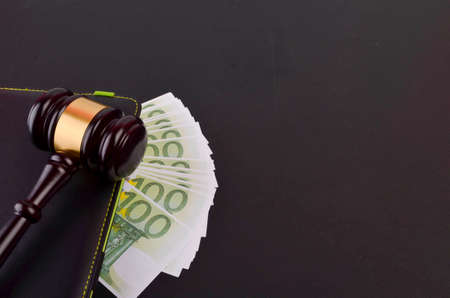 Gavel for judge lawyer with Euro banknotes on black background.