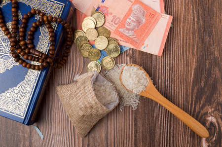 Coins, rosary, Holy Quran and rice in the sack. Zakat concept. Zakat is a form of alm-giving as a religious obligation or tax. Large Arab word right method to read correctly. Stock Photo
