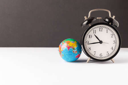 Alarm clock with world globe. World time concept. Selective focus.