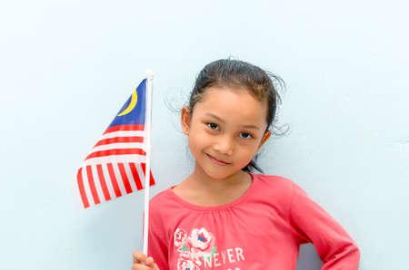 Malay girl holding Malaysia flag. Malaysia independence concept. Selective focus.