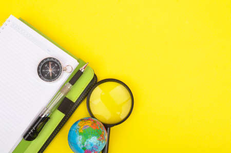 conceptual image. Notebook, compass, magnifying glass, pen and world globe on yellow background.
