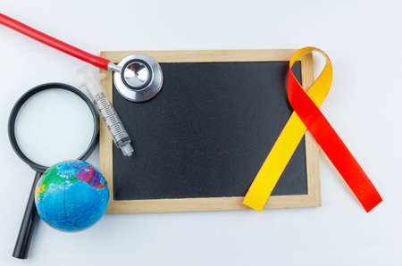 The concept of 'World Hepatitis Day' with yellow and red ribbon, world globe, stethoscope, syringe, magnifying glass and black board for your text. Stok Fotoğraf