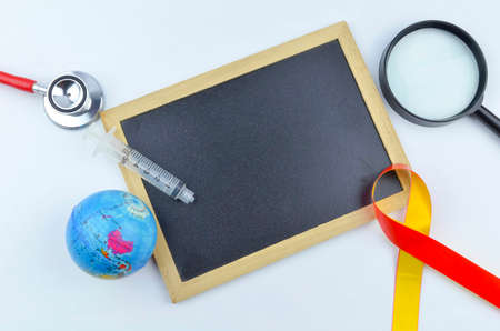 The concept of 'World Hepatitis Day' with yellow and red ribbon, world globe, stethoscope, syringe, magnifying glass and black board for your text. 免版税图像