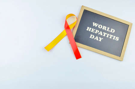 The concept of 'World Hepatitis Day' July 28th on blackboard. Red and yellow ribbon is a symbol of world hepatitis day