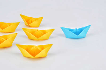 Leadership concept with a blue paper ship leading among yelllow ships 版權商用圖片