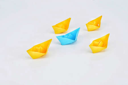 Leadership concept with a blue paper ship leading among yelllow ships
