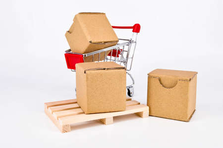 Cardboard boxes,shopping cart and wooden pallet on white background. Warehouse, shipping, cargo and delivery concept.