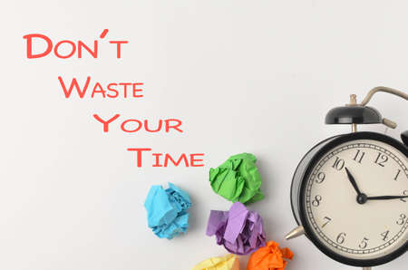 Dont Waste Your Time written with alarm clock and paper trash on white background. Business quotation. Selective focus. Imagens