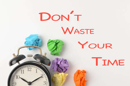 Dont Waste Your Time written with alarm clock and paper trash on white background. Business quotation. Selective focus.
